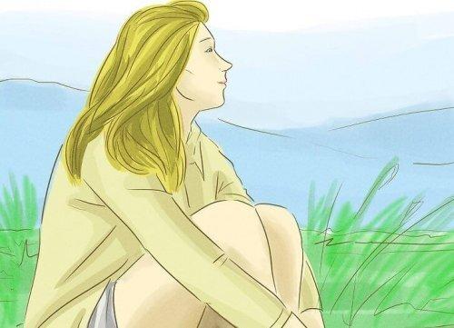Femme seule assise sur l'herbe