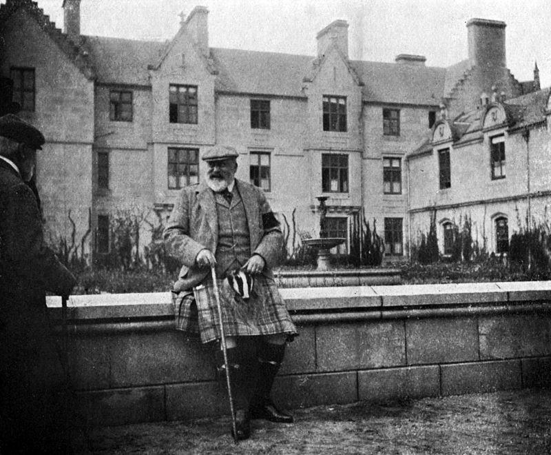 Édouard VII portant un kilt et une canne est assis sur un muret devant une maison à trois étages.