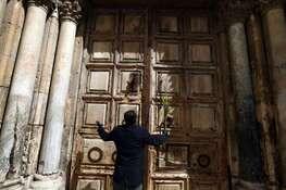 Un chrétien orthodoxe tient une palme devant les portes fermées de l'église du Saint-Sépulcre, le 12 avril à Jérusalem.