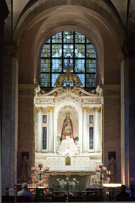 Photographie de la chapelle de Notre-Dame des Miracles et des Vertus. La statue de la Vierge à l'Enfant, l'un et l'autre couronnés, drapée dans un manteau rouge, est placée au centre d'un retable en marbre blanc. Un vitrail emplit la baie au-dessus du retable. Des fleurs et de nombreux cierges se trouvent devant l'autel. Les murs de la chapelle sont couverts d'ex-voto. Deux fidèles prient devant l'autel.