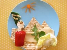Cut unpeeled cucumber in half, with the top cut at a sharp angle - the hat.  ● cucumber, unpeeled, cut into thin strips - eyebrow and pupil.  ● cheese - face  ● red pepper, cut a quarter - the body.  ● cheese - decoration hat and background.  ● wet matzo cut into triangles -  pyramids background.  ● Carrots  Lettuce vegetation.  ● half almond - eye: