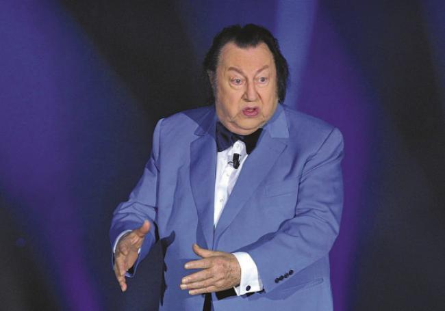 Raymond Devos sur scène avec son éternel costume bleu et son noeud papillon. Photo © TF1/SIPA
