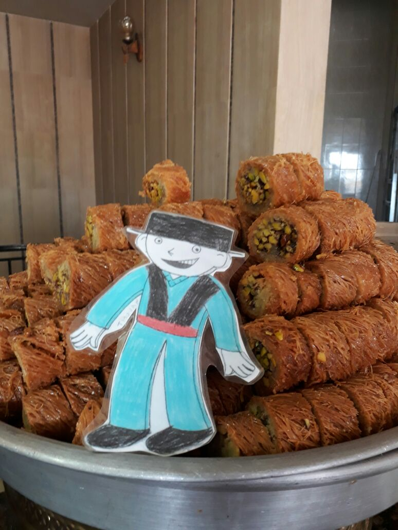 Yara convie Titouan à déguster  les pâtisseries libanaises.