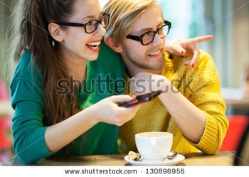 stock-photo-young-couple-in-cafe-laughing-130896956