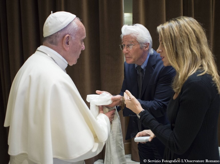 "This handout picture released by the Vatican press office shows Pope Francis (L) meeting with   US actor Richard Gere and girlfriend Alejandra Silva prior a meeting with the participants of the Sixth World Congress of Pontifical Foundation Scholas Occurrentes, on May 29, 2016 in Vatican.  Scholas is an international organization of pontifical right approved and created by Pope Francis in Vatican City August 13, 2013. It combines technology with art and sport to promote social integration and culture of encounter for peace. / AFP PHOTO / OSSERVATORE ROMANO / HO / RESTRICTED TO EDITORIAL USE - MANDATORY CREDIT ""AFP PHOTO / OSSERVATORE ROMANO"" - NO MARKETING NO ADVERTISING CAMPAIGNS - DISTRIBUTED AS A SERVICE TO CLIENTS"