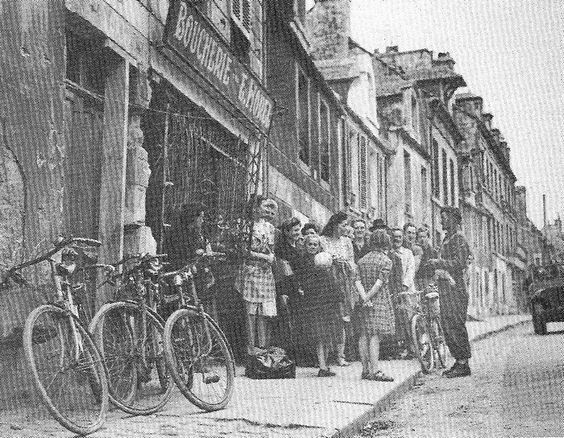 The Lance Corporal ER Sandie, talks to civilians in front of the butcher's of E. Hore at 17, Rue de  Bayeux. (Caen):