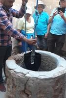 Abdou monte de l'eau dans une jarre en pneu