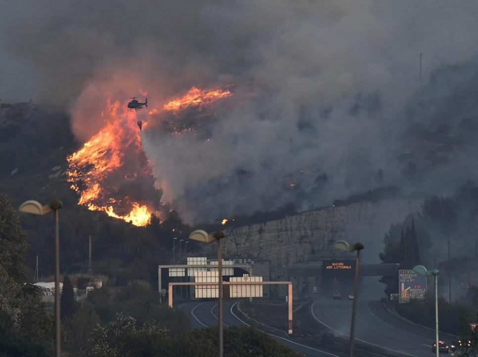 Près de Vitrolles, un hélicoptère lutte contre les flammes alors que l'incendie s'approche de l'autoroute.