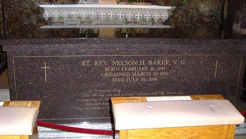 Photo d'une tombe en grès, sous un autel, avec inscription en lettres dorées
