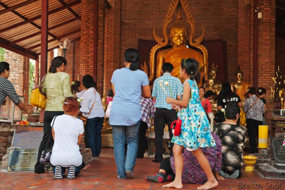 La vénération à Bouddha n'attend pas le nombre des années. Cette jeune fille lotus et baguette d'encens à la main s'apprête à faire une offrande tandis que les adultes sont déjà recueillis et prosternés devant Bouddha.