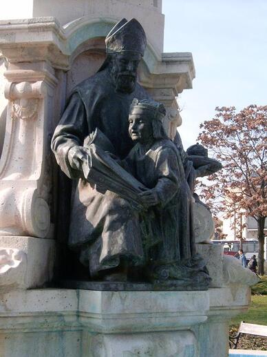 Statue en bronze représentant un évêque assis faisant la lecture un enfant portant une couronne.