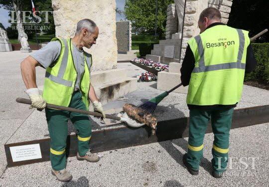 Les agents de la ville ôtent les reliefs dont le rouleau de viande kebab mis à cuire sur le socle du monument aux morts des Glacis . Photo Arnaud CASTAGNE