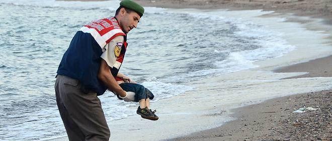 Un policier porte le corps d'Aylan Kurdi retrouvé mort sur la plage de Bodrum, en Turquie. Son frère âgé de 5 ans et sa mère seraient morts noyés eux aussi en tentant de rejoindre Kos en Grèce. Ils venaient de Kobane.