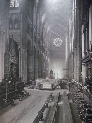 Photographie en noir et blanc de l'intérieur d'une cathédrale, au chœur bordé de deux rangs de stalles de chaque côté.