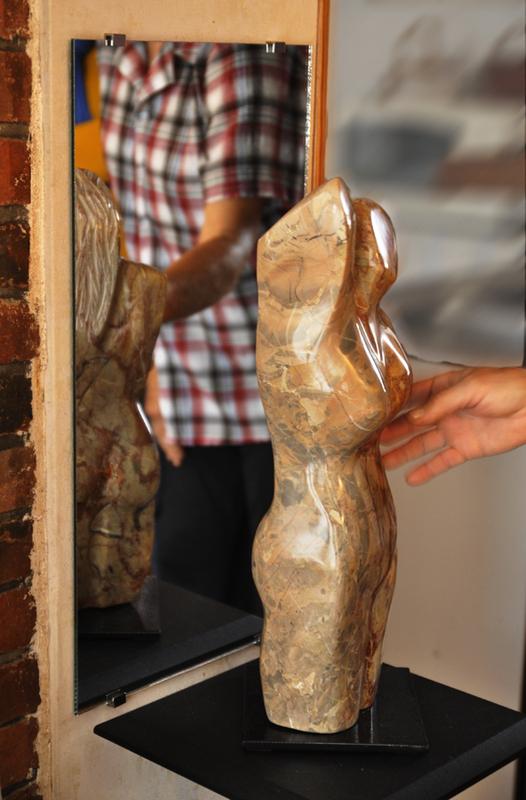 une main caresse une sculpture en pierre