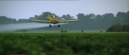 avion pulvérisant du Roundup sur des champs de culture OGM