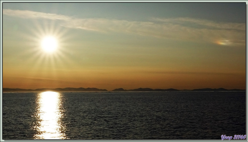 Soleil de presque minuit avec un photométéore rare : un nuage iridescent - Mer de Baffin - Nunavut - Canada