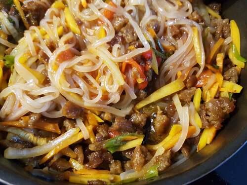 BIBIM GUKSU - Nouilles sautées en sauce aigre-douce piquante au Gochujang, pomme, miel, Xylitol, huile de sésame, vinaigre de pomme & soja avec garnitures