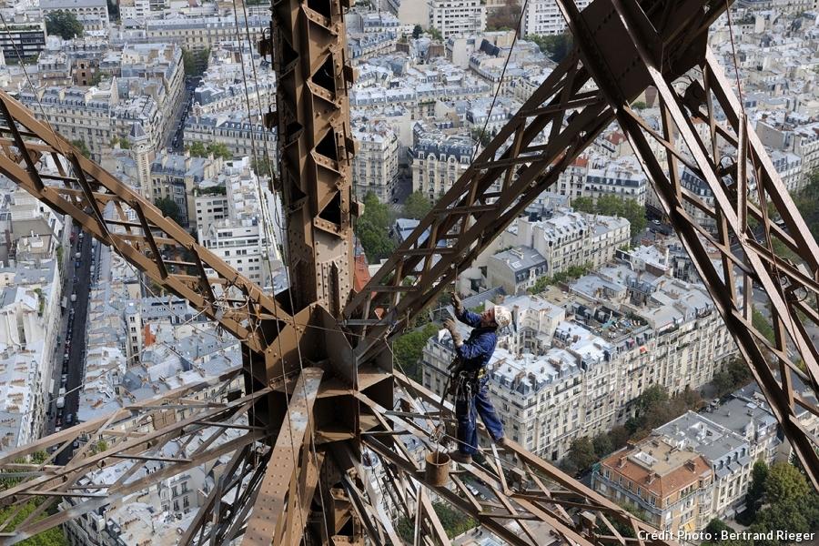 Un peintre travaille sur la tour Eiffel