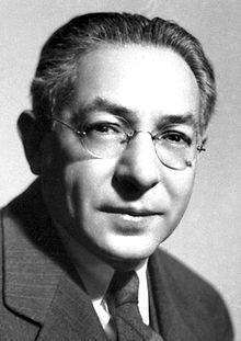 Photo en noir et blanc. Visage d'un homme portant des lunettes et un complet.