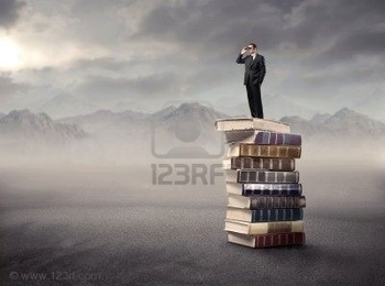 8054405-businessman-standing-on-a-stack-of-books-in-the-mountains-and-using-binoculars