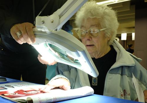 Une personne âgée teste une loupe avec éclairage lors du BrailleTech 2015.