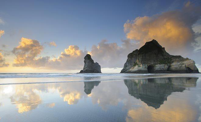 La plage de Wharariki beach est l'une des plus belles du pays. Au petit matin, le reflet des rochers sur le sable humide est remarquable.