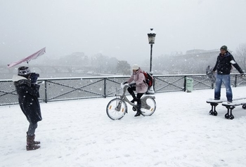 621572_a-woman-cycles-on-a-velib-self-service-public-bicycle-as-tourists-take-photos-during-a-snowfa