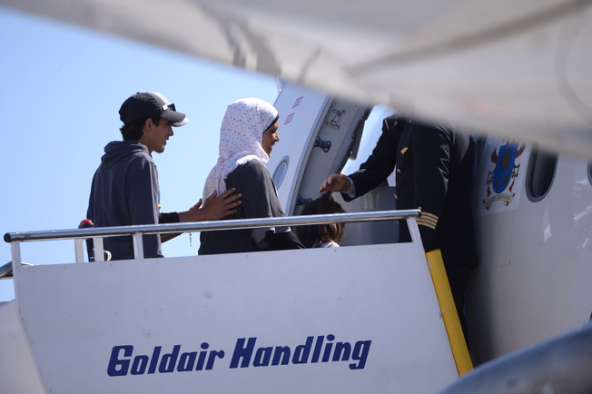 "A group of Syrian refugees board a plane with Pope Francis on April 16, 2016 at the airport of Mytilene, in the Greek island of Lesbos. Twelve Syrian refugees were accompanying Pope Francis on his return flight to Rome after his visit to Lesbos on Saturday and will be housed in the Vatican, the Holy See said. ""The pope has desired to make a gesture of welcome regarding refugees, accompanying on his plane to Rome three families of refugees from Syria, 12 people in all, including six children,"" a Vatican statement said. AFP PHOTO POOL / FILIPPO MONTEFORTE / AFP PHOTO / POOL / FILIPPO MONTEFORTE"