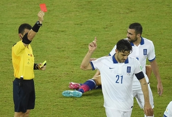 655341-greece-s-midfielder-kostas-katsouranis-2nd-r-is-given-the-red-card-after-a-foul-on-japan-s-midfielde