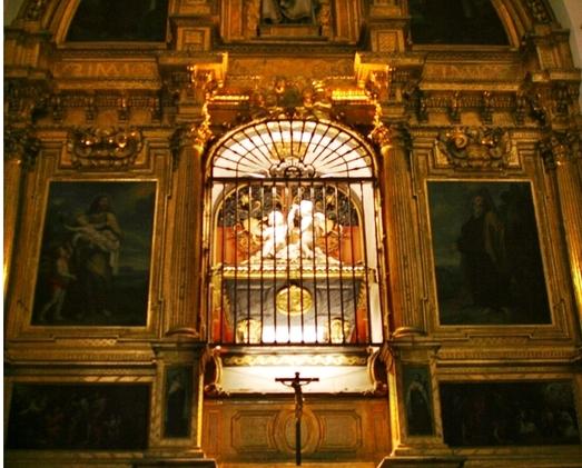 Tombeau ouvragé et éclairé situé dans une église.