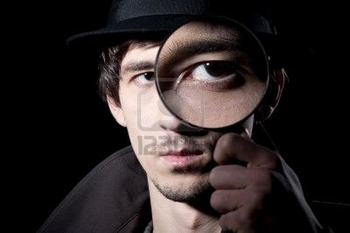 8654999-private-detective-watching-through-a-magnifying-glass-isolated-on-a-black-background