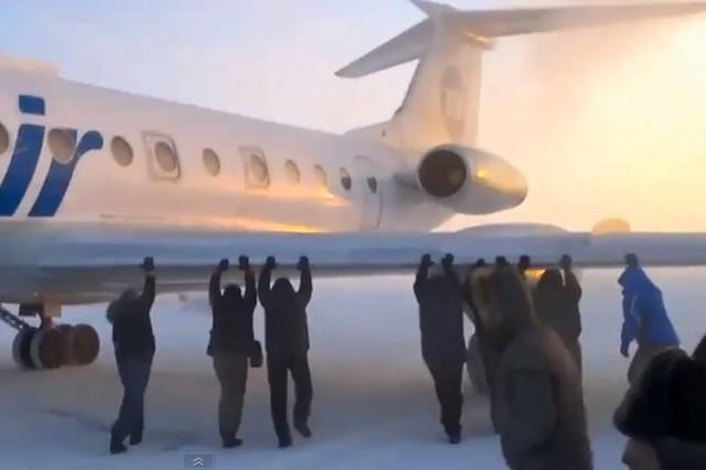 Des passagers russes ont dû pousser leur avion pour qu'il puisse décoller, le... (Image tirée de YouTube)