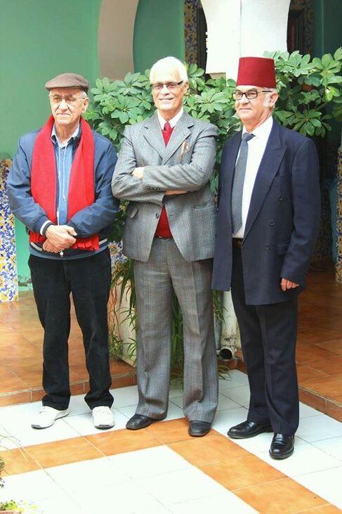L'image contient peut-être: 3 personnes, personnes souriantes, personnes debout et costume
