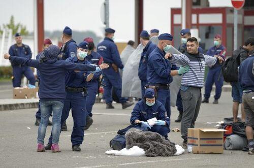 Des soldats et des policiers hongrois fouillent des réfugiés et des migrants entrant dans le pays à Beremend, un village situé le long de la frontière avec la Croatie.