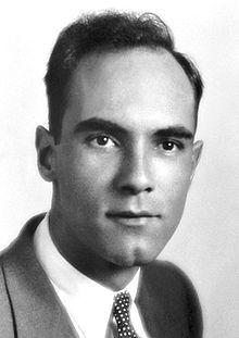 Photo en noir et blanc. Visage d'un homme aux cheveux foncés portant un complet.