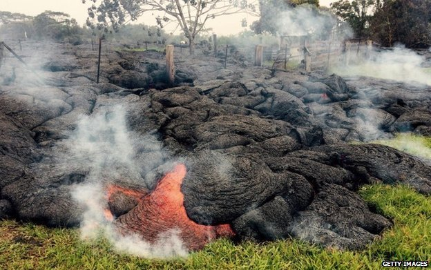Lava flow burns through thick vegetation and a fence