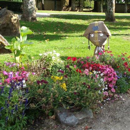 Un épouvantail très original parmi les fleurs de la ville de Bagneux