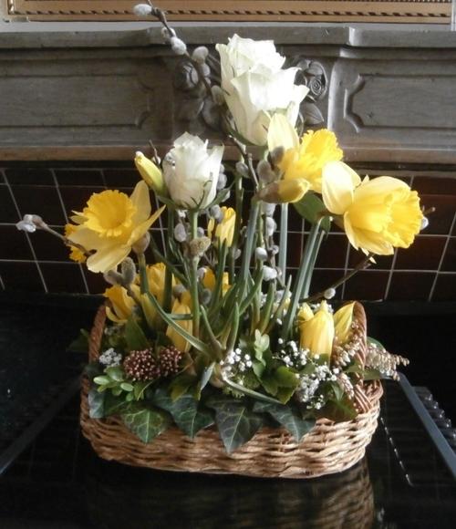 dans une vannerie ovale, une composition des roses blanches, jonquilles, tulipes jaunes, saule marsault, lierre