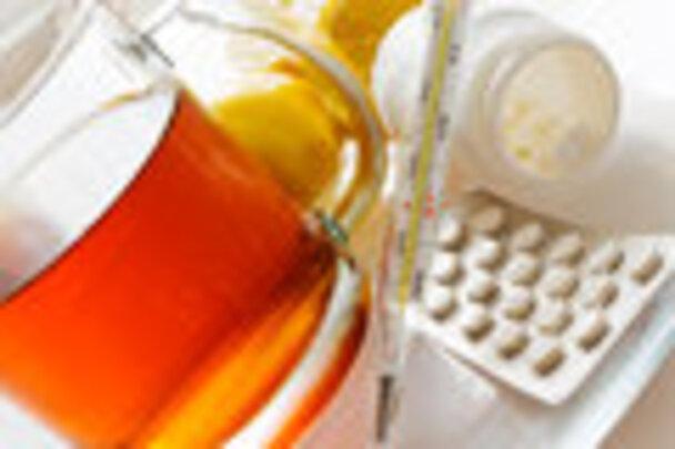 Thé avec des citrons et pilules de grippe avec le thermomètre remède de grippe Image stock