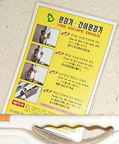 Une plaquette explicative de l'utilisation d'un dispositif d'évacuation de chambre d'hôtel en Corée. Illustré, en quatre langues.