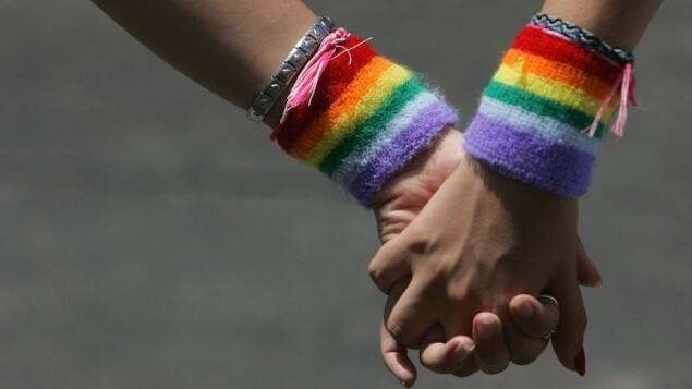 Un couple de lesbiennes se tient la main durant la marche des Fiertés de Tel Aviv le 3 juin 2016 (Crédit : David Silverman/Getty Images via JTA, File)