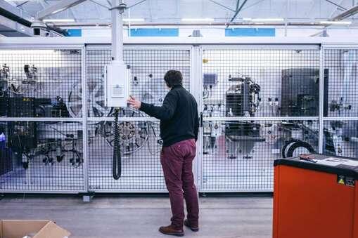 """Un ouvrier et le directeur de """"la Coop des masques"""" réparent une machine à l'arrêt. France, Guingamp, 15 février, 2020."""
