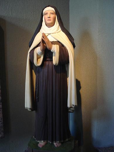 Statue polychrome d'une religieuse debout et en prière.