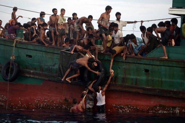 Des réfugiés rohingyas recueillent de la nourriture larguée par un hélicoptère thaïlandais en mer d'Andaman, le 14 mai 2015 (AFP / Christophe Archambault)