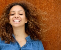 Portrait of a beautiful young woman smiling with curly hair