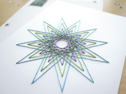 Carte Noël brodée main motif étoile fils tendus brillants bleu, vert et violet detail
