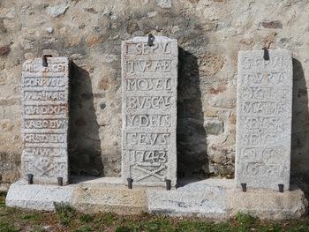 """Adossées à l'Église, ces trois stèles funéraires. Au milieu : """"sépulture de Miquel Buscal et des siens"""""""