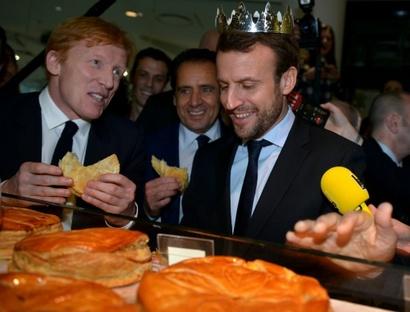 Le ministre de l'Economie Emmanuel Macron goûte une galette des rois le premier jour des soldes à Paris, le 6 janvier 2016