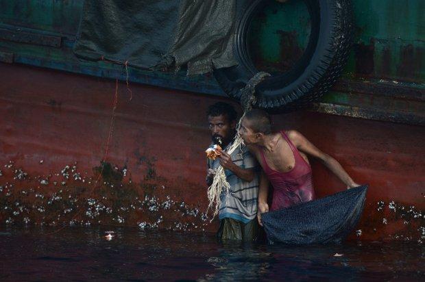 Des réfugiés rohingyas mangent de la nourriture larguée par un hélicoptère thaïlandais en mer d'Andaman, le 14 mai 2015 (AFP / Christophe Archambault)